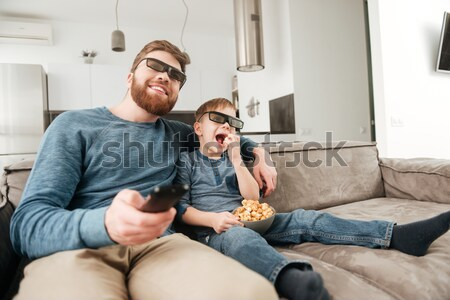 Foto stock: Little boy watching TV with 3d glasses and holding popcorn