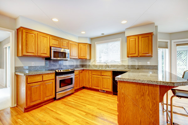 Foto stock: New classic wood large kitchen with grey countertop.