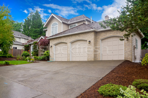 Foto stock: Large beige house with three car garage and large driveway.