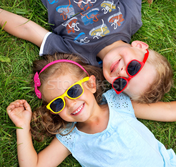 Foto stock: Picture presenting kids relaxinng on the grass
