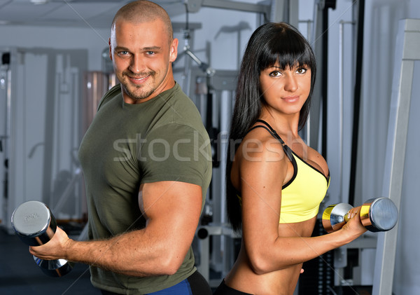 Foto stock: Man and woman are doing exercises in a sport club.